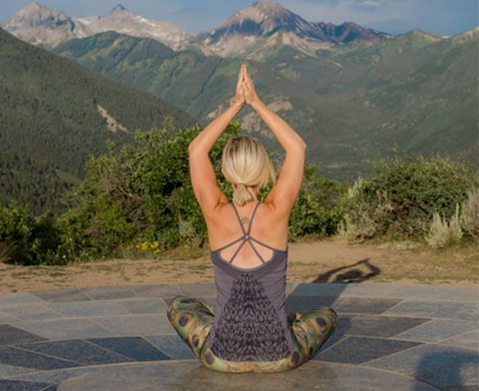 Person doing a yoga pose in the mountains